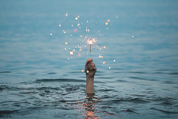 Hand emerging from the ocean holding a lit sparkler